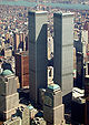 Aerial view of two 110-story twin towers; the building have gray, steel exteriors, and the structure on the left is topped by a large antenna. Several skyscrapers are visible surrounding the two towers.